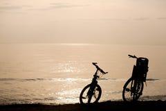 Σκιαγραφίες των ποδηλάτων στην ακτή Στοκ Εικόνες