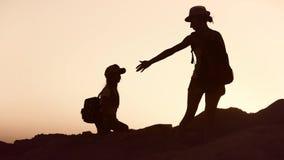 Σκιαγραφίες των τουριστών μητέρων και παιδιών που στο ηλιοβασίλεμα Mom και κόρη στα φέρνοντας σακίδια πλάτης θερινών διακοπών απόθεμα βίντεο