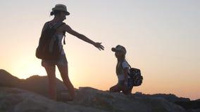 Σκιαγραφίες των τουριστών μητέρων και παιδιών που στο ηλιοβασίλεμα Mom και κόρη στα φέρνοντας σακίδια πλάτης θερινών διακοπών φιλμ μικρού μήκους