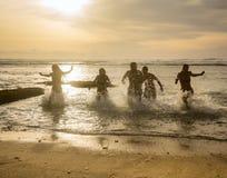 Σκιαγραφίες των φίλων που τρέχουν έξω του ωκεανού Στοκ φωτογραφία με δικαίωμα ελεύθερης χρήσης