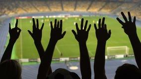 Σκιαγραφίες των χεριών ανεμιστήρων ποδοσφαίρου κατά τη διάρκεια της αντιστοιχίας, συσσωρευμένο γήπεδο ποδοσφαίρου, αθλητισμός απόθεμα βίντεο
