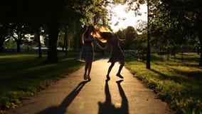 Σκιαγραφίες δύο κοριτσιών που περπατούν στην αλέα απόθεμα βίντεο