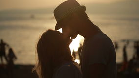 Σκιαγραφημένη λαβή ζευγών μεταξύ τους και φιλί στην παραλία ημερομηνία στην προκυμαία απόθεμα βίντεο