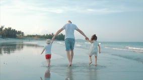 Σκιαγραφημένη ευτυχής οικογένεια που παίζει και που έχει τη διασκέδαση στην παραλία στο ηλιοβασίλεμα o Ευτυχής ελευθερία οικογενε απόθεμα βίντεο