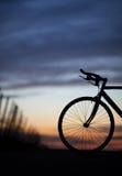 Σκιαγραφημένο ποδήλατο φυλών στο ηλιοβασίλεμα Στοκ φωτογραφία με δικαίωμα ελεύθερης χρήσης
