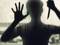 Σκιερός αριθμός με ένα μαχαίρι πίσω από το γυαλί Στοκ Εικόνες