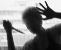 Σκιερός αριθμός με ένα μαχαίρι πίσω από το γυαλί Στοκ εικόνα με δικαίωμα ελεύθερης χρήσης