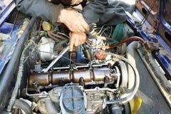 Σκλήρυνση των βαλβίδων με ένα αυτόματος-φωτιστικό στο γκαράζ σε ένα παλαιό αυτοκίνητο στοκ φωτογραφία