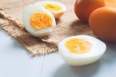 Σκληρά βρασμένα αυγά με τα ακατέργαστα αυγά, τη διατροφή και τα υγιή τρόφιμα Στοκ φωτογραφία με δικαίωμα ελεύθερης χρήσης
