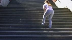 Σκληρά για να αναρριχηθεί στα σκαλοπάτια για το παχύσαρκο κορίτσι, νίκη πέρα από την κούραση για την επίτευξη στόχου απόθεμα βίντεο