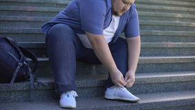 Σκληρά για τον παχύ νεαρό άνδρα για να δέσει τα κορδόνια, οι παχύσαρκοι άνθρωποι προκλήσεων αντιμετωπίζουν κάθε μέρα φιλμ μικρού μήκους