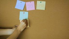 Σκληρά εργαζόμενος για να κάνει τα χέρια καταλόγων που οι κολλώδεις σημειώσεις για την αστεία ζωτικότητα πινάκων καρφιτσών φιλμ μικρού μήκους