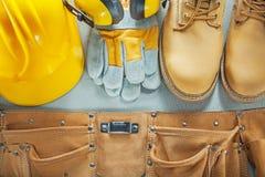 Σκληρά καλύμματα αυτιών μποτών γαντιών ασφάλειας ζωνών εργαλείων καπέλων στη συγκεκριμένη πλάτη Στοκ Εικόνα