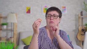 Σκληρά της ακούοντας στοχαστικής γυναίκας που κρατά μια συνεδρίαση ενίσχυσης ακρόασης στο καθιστικό φιλμ μικρού μήκους
