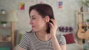 Σκληρά της νέας γυναίκας ακρόασης με την ενίσχυση ακρόασης στα χαμόγελα αυτιών της απόθεμα βίντεο
