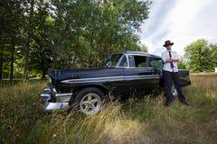 Σκληρός άνδρας με το εκλεκτής ποιότητας αυτοκίνητό του Στοκ Εικόνα