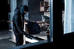 Σκληρός διαρρήκτης που κλέβει ένα lap-top από τον πίνακα στοκ εικόνες