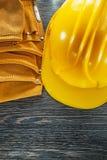 Σκληρό ζευγάρι καπέλων ζωνών κατασκευής δέρματος των γαντιών ασφάλειας στο ξύλο Στοκ Εικόνες
