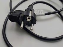 Σκοινί της σύνδεσης της παροχής ηλεκτρικού ρεύματος των οικιακών συσκευών του μαύρου χρώματος με να στηρίξει στοκ φωτογραφίες