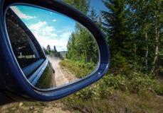 Σκονισμένος δρόμος στον οπισθοσκόπο καθρέφτη στο μπλε αυτοκίνητο στοκ φωτογραφία