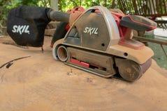 Σκονισμένο ηλεκτρικό sander εμπορικών σημάτων Skil απαλύνει επάνω την τροπική ξυλεία μέσα στοκ φωτογραφία με δικαίωμα ελεύθερης χρήσης