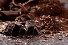 Σκοτεινά ξέσματα σοκολάτας και ψεκασμένη σκόνη κακάου Στοκ εικόνα με δικαίωμα ελεύθερης χρήσης