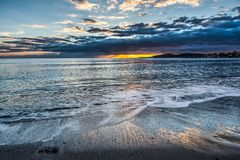 Σκοτεινά σύννεφα και λάμποντας ήλιος πέρα από την ακτή Alghero στο ηλιοβασίλεμα Στοκ φωτογραφίες με δικαίωμα ελεύθερης χρήσης