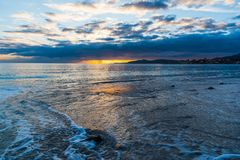 Σκοτεινά σύννεφα και λάμποντας ήλιος πέρα από τη θάλασσα στο ηλιοβασίλεμα Στοκ Φωτογραφία