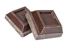 Σκοτεινά τετραγωνικά κομμάτια σοκολάτας σε ένα άσπρο υπόβαθρο στοκ εικόνα