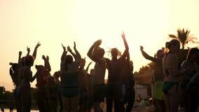 Σκοτεινές σκιαγραφίες των ανθρώπων που χορεύουν, έχοντας τη διασκέδαση στην παραλία, το καλοκαίρι, στο ηλιοβασίλεμα κόμμα παραλιώ φιλμ μικρού μήκους