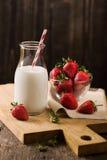 Σκοτεινή ακόμα ζωή με το γάλα και τη φράουλα στο τραχύ ξύλο Στοκ εικόνες με δικαίωμα ελεύθερης χρήσης