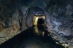 Σκοτεινή ανατριχιαστική βρώμικη πλημμυρισμένη εγκαταλειμμένη σήραγγα ορυχείων στοκ φωτογραφίες