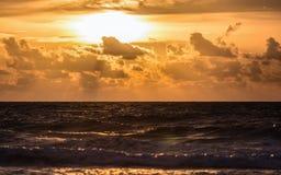 Σκοτεινή θάλασσα με το χρυσό νεφελώδη ουρανό ηλιοβασιλέματος Στοκ φωτογραφίες με δικαίωμα ελεύθερης χρήσης