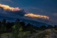 Σκοτεινή θύελλα σύννεφων Βροχή που έρχεται στον ουρανό κατά την αγροτική οδική άποψη Στοκ Φωτογραφίες