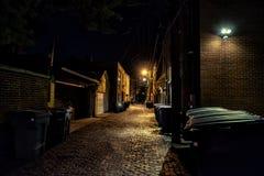 Σκοτεινή και μυστηριώδης αστική αλέα τούβλου κυβόλινθων πόλεων τη νύχτα στοκ φωτογραφίες