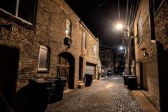 Σκοτεινή και μυστηριώδης αστική αλέα τούβλου κυβόλινθων πόλεων τη νύχτα στοκ εικόνες