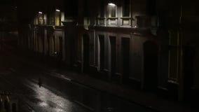 Σκοτεινή οδός με λίγους θέσεις και ανθρώπους λαμπτήρων που τρέχουν μέσω της δυνατής βροχής κατά τη διάρκεια μιας σκοτεινής νύχτας απόθεμα βίντεο