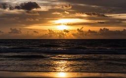 Σκοτεινή σκηνή της θάλασσας με το χρυσό νεφελώδη ουρανό ηλιοβασιλέματος Στοκ Εικόνα