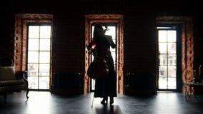 Σκοτεινή σκιαγραφία μιας γυναίκας που παίζει το βιολοντσέλο στο στούντιο απόθεμα βίντεο