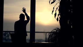 Σκοτεινή σκιαγραφία της επιχειρησιακής γυναίκας έβαλε το χέρι της στο γυαλί ενός μεγάλου παραθύρου γραφείων είναι κουρασμένη, ανα απόθεμα βίντεο