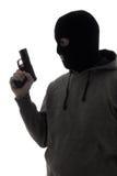 Σκοτεινή σκιαγραφία του εγκληματικού ατόμου στο πυροβόλο όπλο εκμετάλλευσης μασκών που απομονώνεται επάνω Στοκ Φωτογραφίες