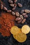 Σκοτεινή σκόνη κακάου, φασόλια κακάου και νομίσματα σοκολάτας Στοκ Εικόνες