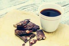 Σκοτεινή σοκολάτα με τα καρύδια και μια κούπα του μαύρου καφέ σε τσαλακωμένο χαρτί Στοκ Εικόνα