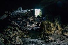 Σκοτεινή σπηλιά με τα βήματα της σκάλας και του φωτός από την είσοδο Στοκ εικόνα με δικαίωμα ελεύθερης χρήσης