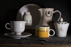 Σκοτεινή στάμνα γάλακτος ύφους χωρών, κορφολόγος και παλαιά εκλεκτής ποιότητας κούπα στο μαύρο υπόβαθρο Στοκ εικόνες με δικαίωμα ελεύθερης χρήσης