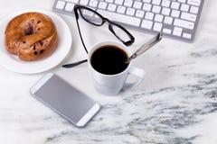 Σκοτεινοί καφές και bagel για το πρόγευμα λειτουργώντας στο σπίτι στο whi Στοκ Φωτογραφία