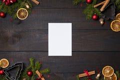 Σκοτεινός αγροτικός ξύλινος πίνακας flatlay - σημειώστε την κάρτα στο υπόβαθρο Χριστουγέννων με το πλαίσιο κλάδων διακοσμήσεων κα στοκ εικόνα με δικαίωμα ελεύθερης χρήσης