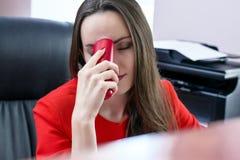 Σκοτεινός-μαλλιαρή ελκυστική επιχειρησιακή γυναίκα στο κόκκινο κοστούμι και κόκκινο τηλεφωνικό διαθέσιμο να πάσσει από τους πονοκ Στοκ Εικόνες