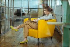 Σκοτεινός-μαλλιαρή συνεδρίαση επιχειρηματιών στη συμπαθητική comfy κίτρινη πολυθρόνα στοκ φωτογραφία με δικαίωμα ελεύθερης χρήσης