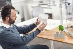 Σκοτεινός-μαλλιαρός μηχανικός που διερευνά το πρότυπο σπιτιών μετά από την εκτύπωση Στοκ Εικόνα